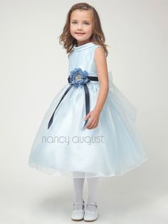 This darling little number has all the simple and extra sweet design details you could ever want! This is the first dress in our flower girl dress collection that introduces this fancy and sophisticated collar! This unique collar rests gently on the collarbone creating a look that is classy and chic! The sleeveless satin bodice compliments this collar well. The full skirt is made with a lovely organza overlay and falls at the natural tea length. To finish the look, a waistband and ribbon…