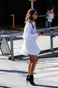 Christine Centenera wears a white mini dress with black heeled ankle boots.
