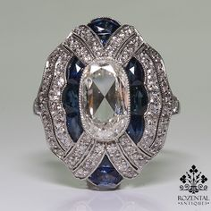 Antique Art Deco Platinum Diamond & Sapphire Ring, USD 9800. Period: Art deco (1920-1935) Composition: Platinum Stones: 1 Old mine cut diamond of H-VS2 quality that weighs 2.04ctw. 80 Old mine cut diamonds of H-VS2 quality that weigh 1.10ctw. 10 natural calibrated French cut sapphires that weigh 0.20ctw. Ring size: 7 ½ Ring face: 23mm by 18mm Rise above finger: 9mm Total weight: 8.8grams –5.7dwt