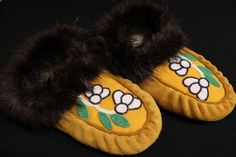 $129.95 Tan coloured hide with yellow toe and white, green and iridescent purple beaded flower design. Beaver trim. Buy them now and save 10% with promocode Kitigan2014