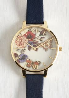 Simple and elegant gold plated stylish watch with a floral pattern face and skinny blue band.