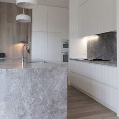 Mim Design kitchen. Ovens etc behind wall panel and done in white to blend in. Could move breakfast prep area to end with a shallow end panel instead of having fridge at end.