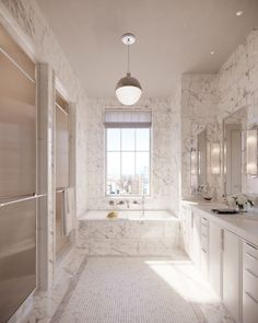 This master bath provides a serene escape from the city, with floor-to-ceiling honed white statuary marble, a Kohler bathtub below a large picture window, and Lefroy Brooks polished-chrome fittings. #bathroom #marble #apartmentbathroom #luxurybathroom