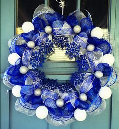 - White, Silver and Royal Blue mesh cover a wire wreath frame with white and silver glittered ornaments as well as royal blue glittered snowflakes. - This wreath is the perfect door decor to set the s