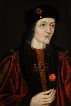 King Henry VII (1457–1509), English School, 16th century. A small half-length portrait of a man, wearing a crimson robe, holding a red rose, and wearing a black hat with jewel.