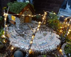 "Solar LED twinkle lights strung over a mosaic stepping stone ""patio"" in a fairy garden"
