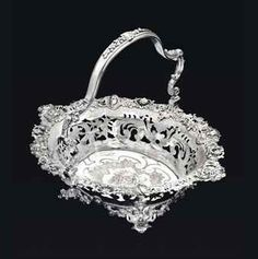 A fine George II silver cake basket, mark of Paul de Lamerie, London, 1739 -  Of large size; shaped-oval, on four cast feet in the form of bearded masks with scrolls & shells issuing from their mouths, with openwork floral garlands between, the everted sides pierced & engraved with foliage & scrolls, with an elaborately cast openwork border with rocaille, stylized sea monster heads, & four masks representing the Four Seasons, the center flat-chased with foliage...15¾ in.  long