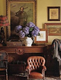 Distinguished entry. Old fashioned - very manly but the flowers add a feminine touch. Plaid lampshade. Interesting how the picture on the table covers the corner of a wall picture.