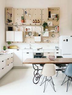 Schöne Küche mit Esszimmer und Lochwand mit Regalen und Behältern