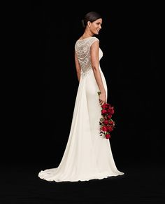 Sleek stretch crepe forms the backdrop for 8,600 pieces of deco-inspired beading along the V-neckline and illusion back of Galina Signature's cap-sleeve wedding dress. Exclusively at David's Bridal.