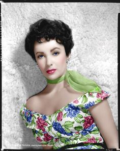 c5ab0e63d053 Elizabeth Taylor with a white cap sleeved dress with pink water lily like  flowers and green leaves and matching pink scarf.