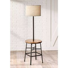 Inspired by industrial and farmhouse looks, this table floor lamp has been fashioned around a four-legged work-stool base.