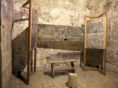 Chair, table and stone tablets in a cell at the Prigioni Nuove prison