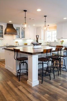 Two pendant lights illuminate a new kitchen island with a countertop made from the wood of an old train car. The island offers additional counter space and a casual dining area. More Fixer Upper before-and-afters.