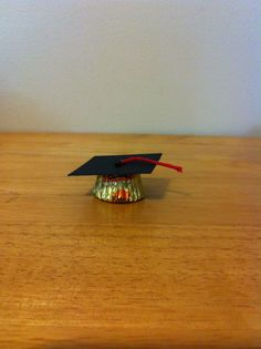 "Here are the preschool graduation treats we made for the class. Top of the hat is 1.75"" x 1.75"" black cardstock, a paper punch circle, and a piece of red twine."