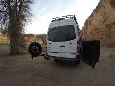 Sprinter with Aluminess rear bumper and swing arms for tire rack and box storage. Photo cred: bearfoot theory
