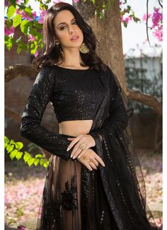 Black and Nude Sequins Embroidered Lehenga features a dhupioni silk blouse with sequins embroidery all over, nude lehenga with black net overlay and sequins embellishments all over alongside a sequins embroidered net dupatta. Pakistani Fashion Party Wear, Indian Fashion Dresses, Dress Indian Style, Indian Designer Outfits, Designer Dresses, Indian Wear, Black Blouse Designs, Netted Blouse Designs, Fancy Dress Design