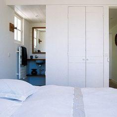 Chambre blanche de 12m2, avec des placards intégrés pour gagner de la place et un cabinet de salle de bains, avec douche, ouvert sur la chambre