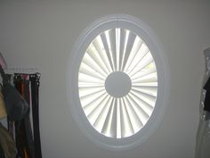 Circular window covered with shutters by The Louver Shop.