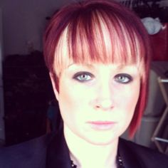 Asymmetrical hair cut with a bold bang. Red with blonde peekaboo highlight