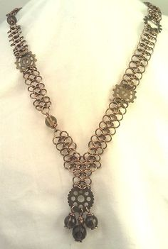 4 in 1 chainmail with bronze-enameled 20 gauge wire. Asymmetrical, with gears and smoky quartz beads.