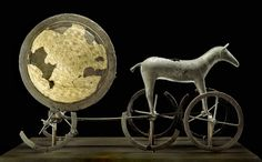 The Trundholm sun chariot (Danish: Solvognen), is a late Nordic Bronze Age artifact discovered in Denmark. It is a representation of the sun chariot, a bronze statue of a horse and a large bronze disk, which are placed on a device with spoked wheels.