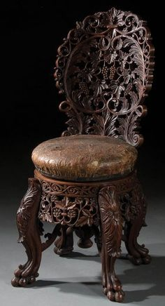 A VERY FINE CONTINENTAL CARVED WALNUT PIANO STOOL late 19th century, of adjustable height, with screw turned leather seat, allover pierced scrolling grape leaf and fruit carved cluster back above a seat raised on four claw footed legs.