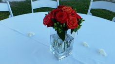 Table center of orange and coral roses with green hypericum berries