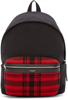 Lightly-structured textile backpack in black. Grosgrain carry handle at top. Adjustable leather shoulder straps with zipper accent. Two-way zip closure at main compartment. Gold logo stamp and leather trim at front zippered patch pocket in red and black plaid felted wool. Padded back panel with logo patch in black leather. Welt pocket at interior. Fully lined. Silver-tone hardware. Tonal stitching. Approx. 12 length x 15