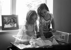 Newborn Hospital Photography  Madison Wisconsin Sisters looking at baby for the first time. So Sweet.