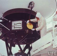 ingeniero instalando el disco de oro donde lleva grabado los sonidos de la tierra como la lluvia el viento el llanto de un bebe, viene el mapa de nuestro sistema solar etc etc
