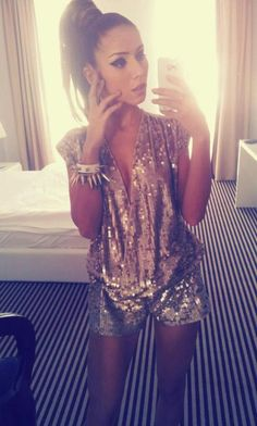 Sequin romper with spiked bracelets.
