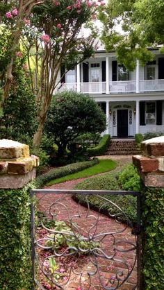 Grand southern home... Pillared white porch, lovely iron gate, brick pavers paved pathway, landscaped garden