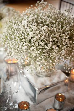 Baby's breath centre pieces with insect brooches flying over.