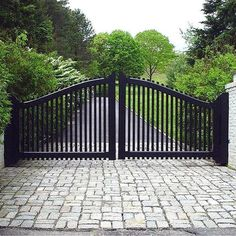 Transitional-style driveway gate with a sleek black finish and contrasting white brick pillars. Driveway entrance gate designed and installed by Tri State Gate in Bedford Hills, New York.