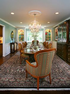 Touches of Modernity.  This elegant and traditional dining room features several Victorian elements: an eye-catching chandelier, ceiling medallion, Oriental-inspired area rug and light, feminine walls. The built-in shelves, accent lighting and colorful, eclectic accessories pull in a touch of fresh, modern style. Design by Barbi Krass