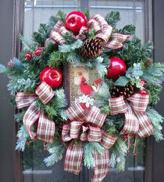 This cardinal Christmas wreath is a cozy combination of plaid ribbon, artificial pine, blue spruce, apples, cherries, pine cones & red berries accented with a bright red cardinal.