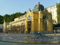 "19th Century playground of the rich and famous    		Colonnade in Mariánské Lázně (Marienbad) spa, Bohemia - Czech  Republic, built 1884-89 with ""singing"" fountain in  foreground."