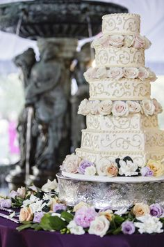 grand wedding cake with gold accents and real roses
