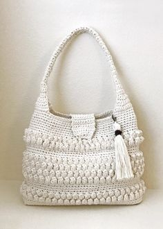 This is a beautiful and easy to make crochet bag. The bobbles and tassel add interesting detail. The pattern looks complicated but is simply made with single and double crochet stitches.The pattern has detailed instructions with pictures of each step for additional help. The pattern is appropriate for an advanced beginner. The bag shown was made with Aran weight yarn (Drops Bomull-Lin) held double, but Worsted Weight held double will also work fine. A suggested yarn is shown below.