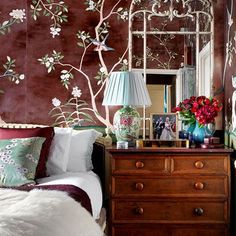 The main bedroom in Hannah Cecil Gurney's west London flat features an ornate cream mirror which elegantly mimics the branches in the pattern of the antiqued 'Badminton' de Gournay wallpaper. Floral bedding as well as a floral lamp build on the theme.