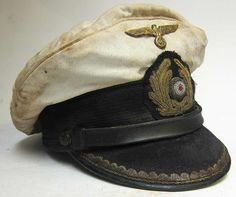 This is a superior version, reproduction of a German Navy U-Boat Submariners Captains Peaked cap with 70+ years of ageing and numerous oil stains and some worn areas as worn by the Captain of a unknown submarine from WWII.  The peak, liner and chinstrap etc. all show good wear and both the inside and outside are oil and dirt stained and aged. Notice the gold emblem and Captains peak ranking are dark and tarnished.  www.warhats.com