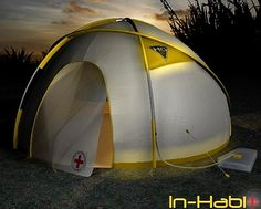 The In-Habit is a lightweight tent made of recycled PET bottles. Lighting is provided by solar panels which light up the low power-high luminosity OLEDs. The tent will also keep occupants warm since it is made of a heat retaining material. Rain water and dew will collect into a expandable bag which can later be tapped for sanitation.