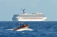 A Coast Guard boat patrols near the disabled cruise ship Carnival Triumph in the Gulf of Mexico as it floats aimlessly about 150 miles off the Yucatan Peninsula after a fire in its engine room.