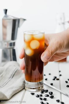 straight on image of man holding glass of kombucha coffee with ice on a white wooden backdrop.