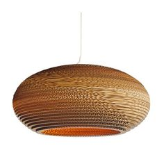 Disc shaped hanging ceiling pendant light made from stacked rings of scrap corrugated cardboard.