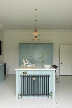White painted wooden floorboards look so perfect with the deVOL Shaker cupboards painted in Trinity Blue