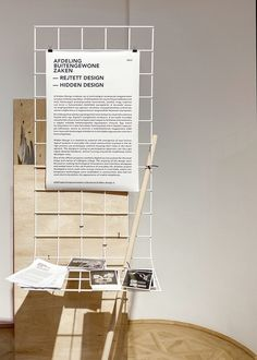 display for handouts and temporary announcements | wood + white metal + black and white paper prints
