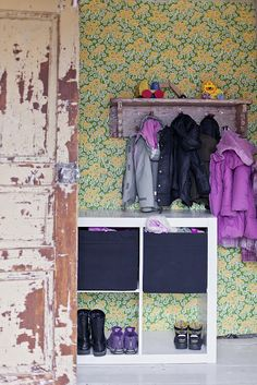 cool crusty door and clothes rack, love the vintage wallpaper it ties it all together!