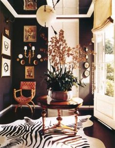 Look at the orchid on this foyer table! The dark floor, dark walls. Zebra Cowhide Rug, the glass door with that incredible handle. The mirrored ceiling! There are so many striking touches in this small space!